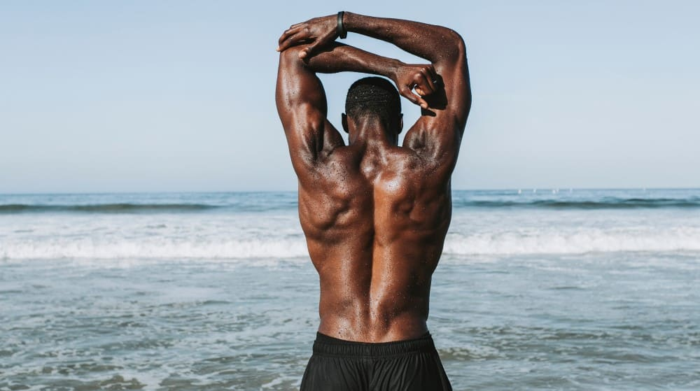 Black man flexing his back for the optimal traps volume