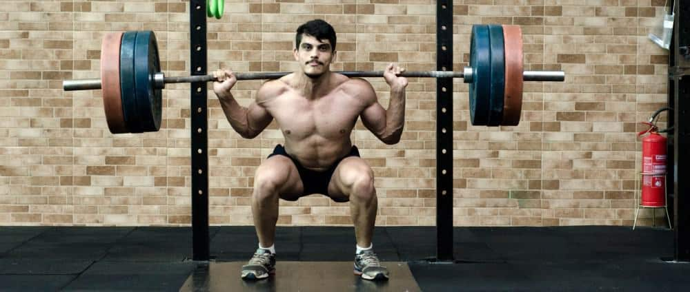 Man doing heavy squats for the optimal hamstrings volume