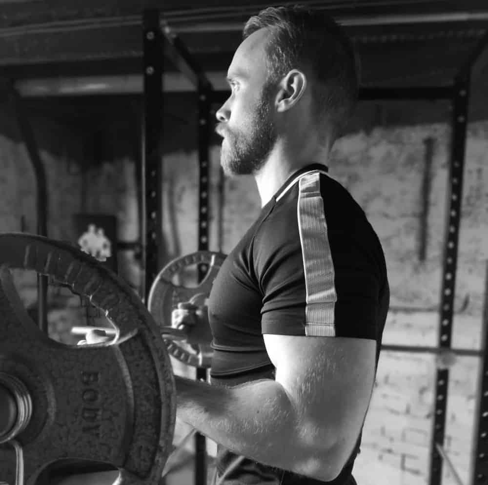 Man doing dumbbell biceps curls for the optimal biceps volume
