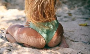 Woman with long blond hair sitting in sand