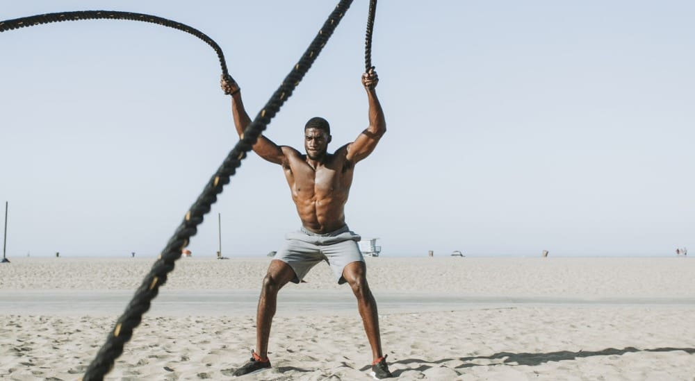 Black man exercising at a beach