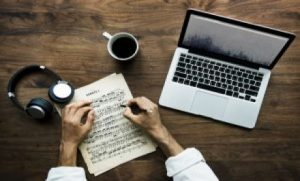 two hands writing on a piece of paper next to a laptopt, headphones and a cup of coffee