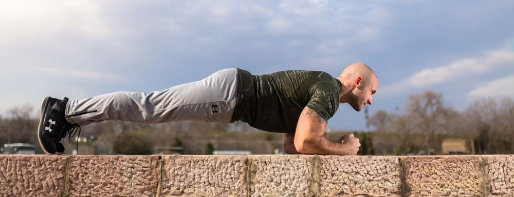 Man doing planks for the optimal abs volume
