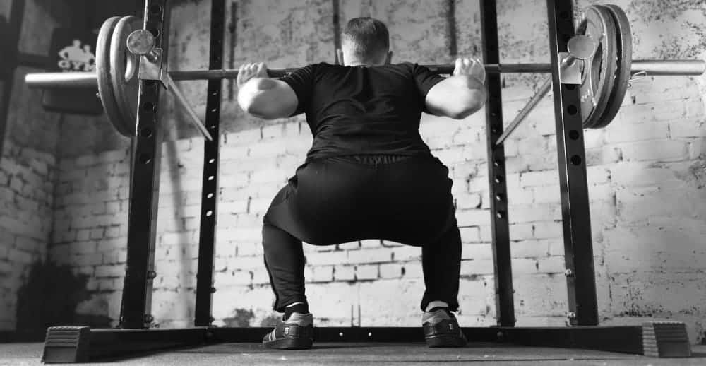 Man doing heavy squats in his High Intensity Training session