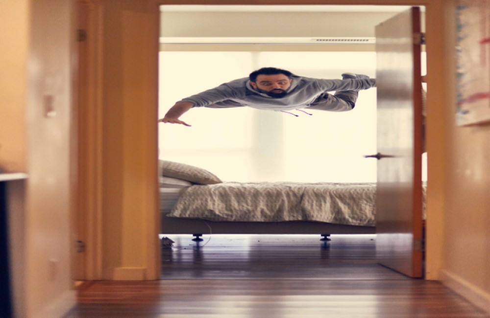man floating above the bed