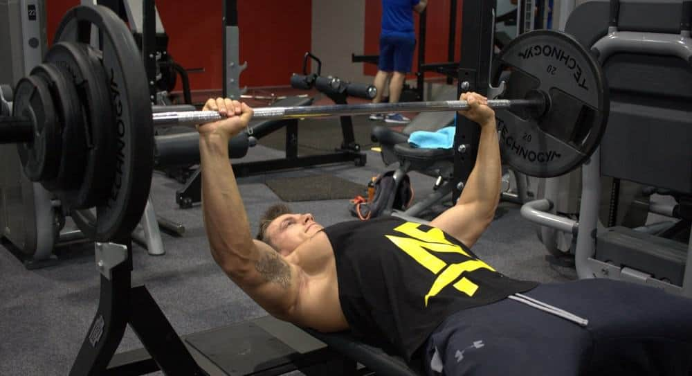 Man doing heavy intense bench press in his HIT workout