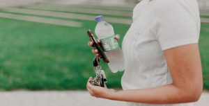 Woman holding a water bottle, keys, and a smartphone