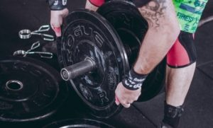 Man plugging off weight plates of the bar