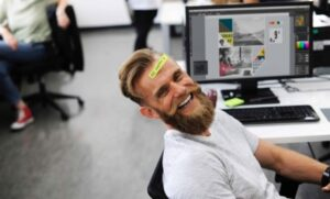 Bearded man sitting at work laughing, enjoying his occupation, while having a sticker attached to his forehead