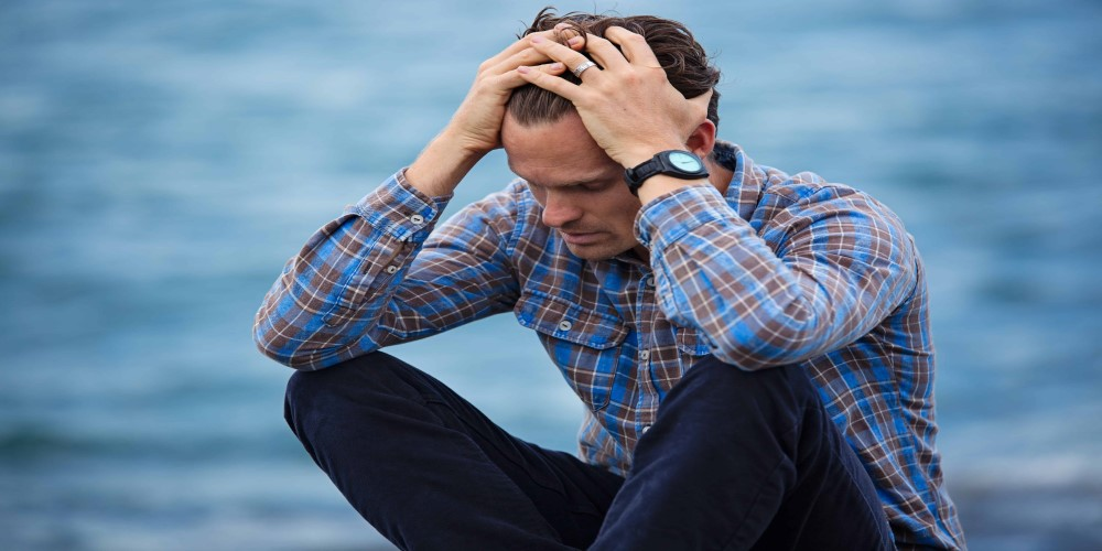 Man sitting next to the sea with his hands holding is head, how to deal with failure