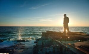 man standing on a cliff at dawn, visualising his dreams depsite of a full-time job