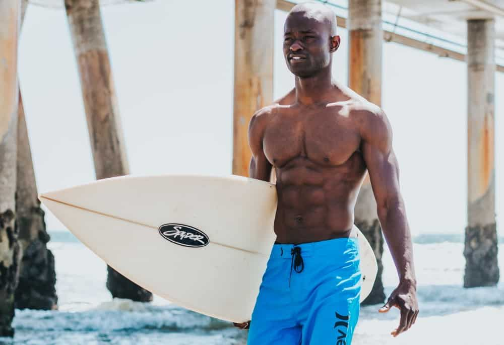 Black man carrying a surfboard